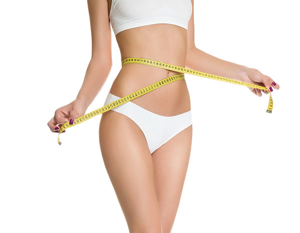 Woman measuring perfect shape of beautiful toned waist healthy
