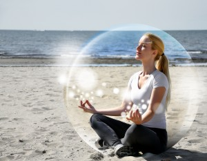 A woman is sitting on the beach inside a bubble with peace and tranquility. She is meditating and there are sparkles.
